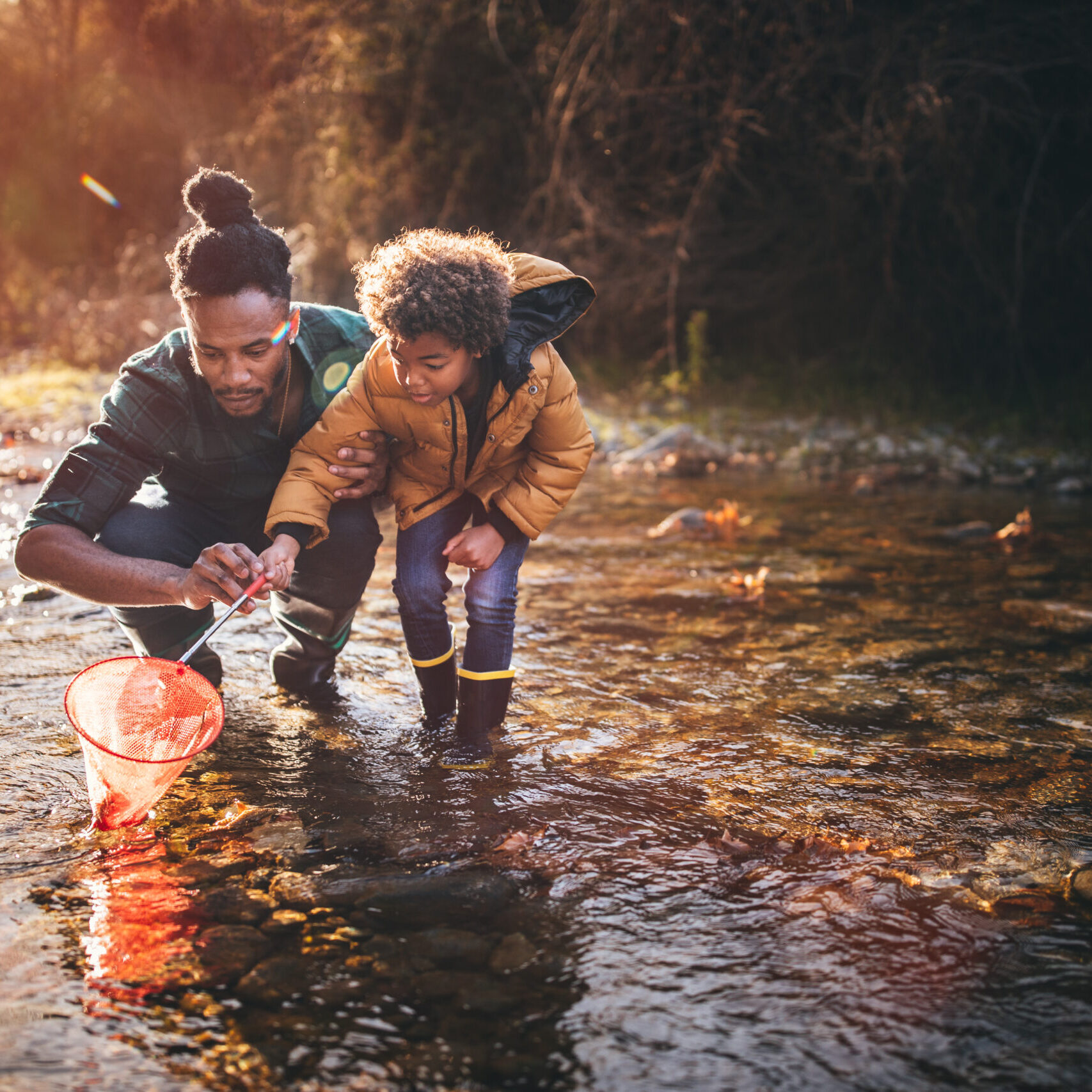 Young dad teaching son how to fish with fishing net in mountain stream at sunset